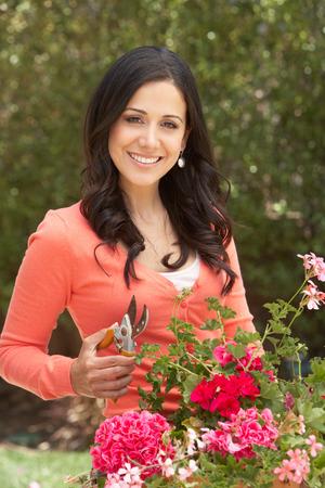 tidying: Hispanic Woman Working In Garden Tidying Pots