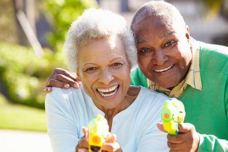 mischevious: Senior Couple Shooting Water Pistols