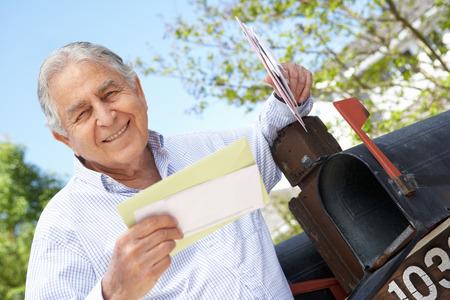 mail man: Senior Hispanic Man Checking Mailbox