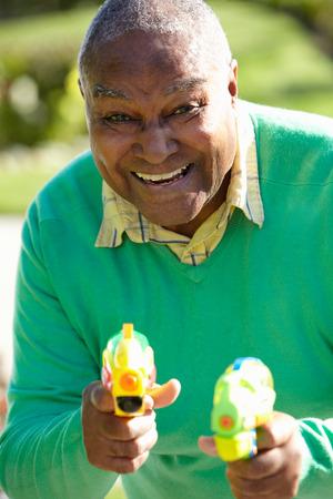 mischevious: Senior Man Shooting Water Pistols Stock Photo