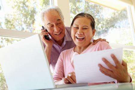 persona llamando: Pareja taiwanesa mayor que trabaja en casa Foto de archivo
