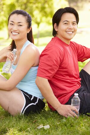 man drinking water: Asian couple resting after exercise