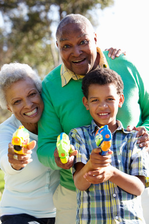 mischevious: Grandparents And Grandson Shooting Water Pistols Stock Photo