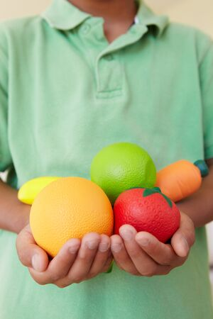 asian preteen: Young boy holding plastic fruit and vegetables Stock Photo