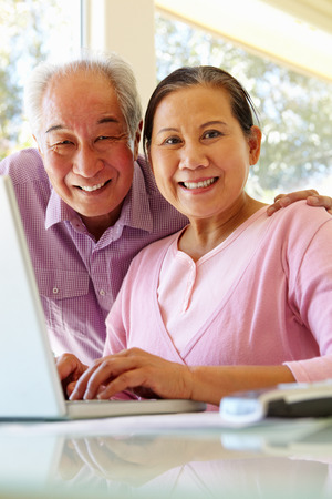 home finances: Senior Taiwanese couple working on laptop Stock Photo