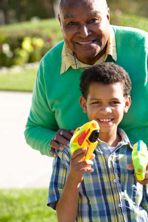 mischevious: Grandfather And Grandson Shooting Water Pistols Stock Photo