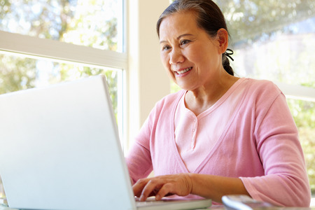 usando computadora: Mujer taiwanesa mayor que trabaja en la computadora portátil Foto de archivo