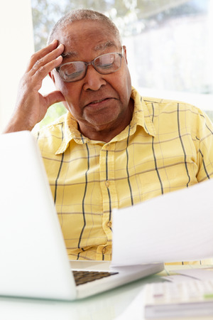 70s adult: Worried Senior Studying Paperwork At Home