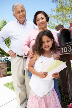 grandparents: Hispanic Grandparents And Granddaughter Checking Mailbox
