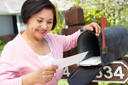 Senior Hispanic Woman Checking Mailbox Foto de archivo