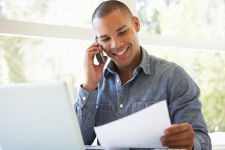 hablando por telefono: Hombre joven en el teléfono usando la computadora portátil en casa