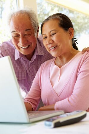 taiwanese: Senior Taiwanese couple working on laptop Stock Photo
