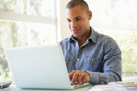usando computadora: Joven usa portátil en casa