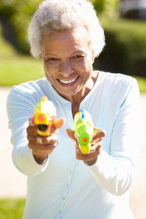 mischevious: Senior Woman Shooting Water Pistols Stock Photo