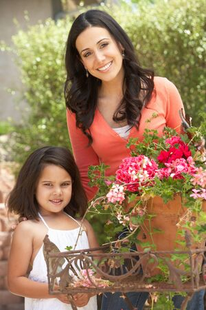 tidying: Hispanic Mother And Daughter Working In Garden Tidying Pots Stock Photo