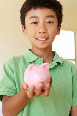 thrifty: Young boy holding piggybank