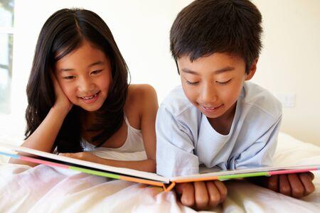 niñas chinas: Asia chica joven y el libro de lectura del muchacho Foto de archivo