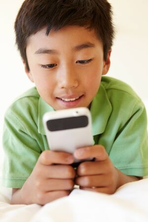 asian preteen: Young boy using smartphone Stock Photo