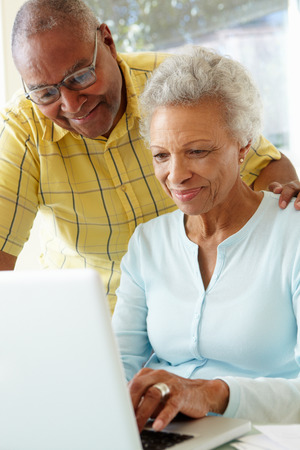 vertical: Senior Couple Using Laptop At Home Stock Photo