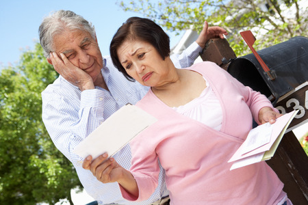 Worried Senior Hispanic Couple Checking Mailbox