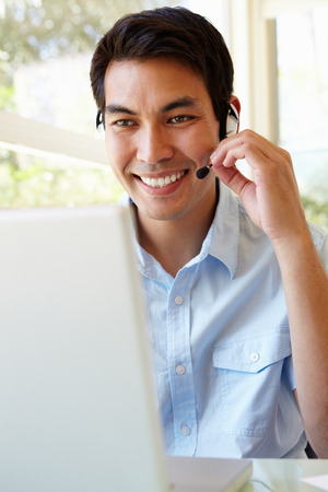 skype: Filipino man using skype Stock Photo