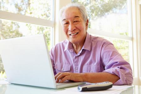 Senior Taiwanese man working on laptop