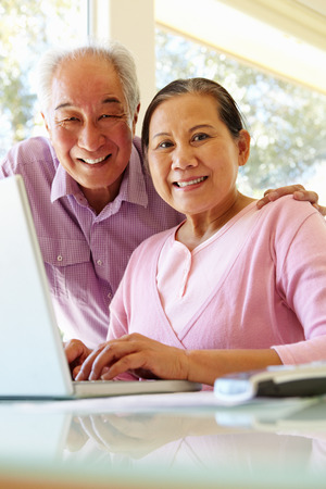 Senior Taiwanese couple working on laptop photo