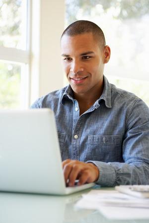 hombres trabajando: Joven usa portátil en casa