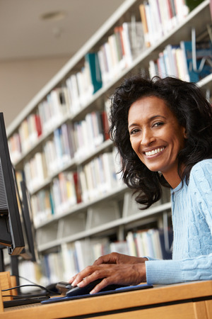 Mid age woman working on computer in library