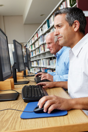 40s adult: Men working on computers in library Stock Photo