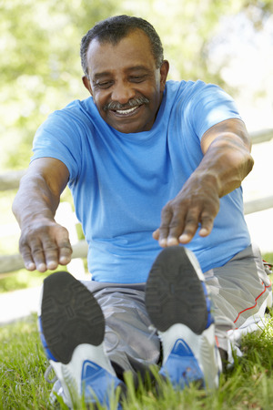 touching toes: Senior African American Man Exercising In Park