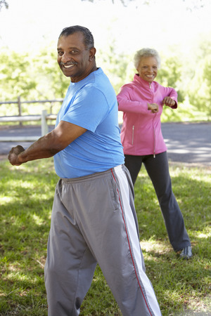 touching toes: Senior African American Couple Exercising In Park