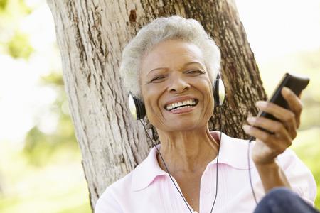 シニアのアフリカ系アメリカ人女性の MP3 プレーヤーに耳を傾ける