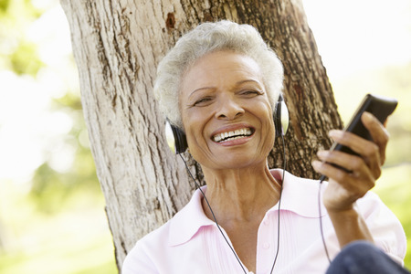 old technology: Senior African American Woman In Listening To MP3 Player
