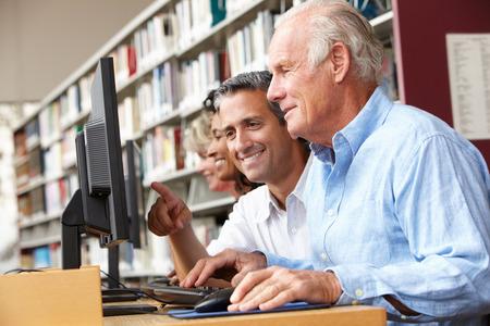 grupo de hombres: Los estudiantes trabajan en los ordenadores en la biblioteca