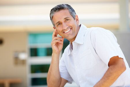 gray haired: Portrait man sitting outdoors