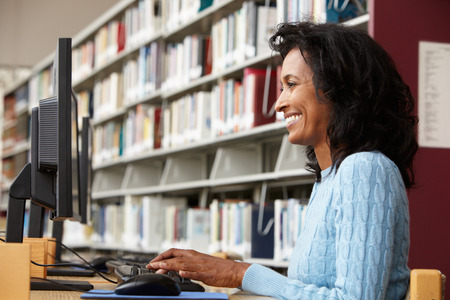 coursework: Mid age woman working on computer in library