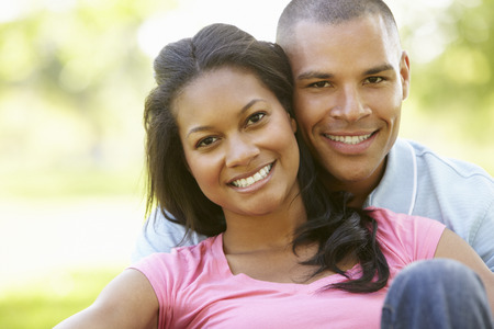 african american woman smiling: Portrait Of Romantic Young African American Couple In Park
