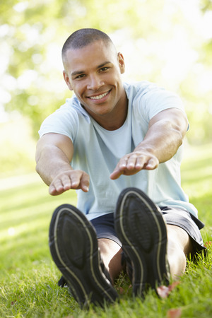 touching toes: Young African American Man Exercising In Park