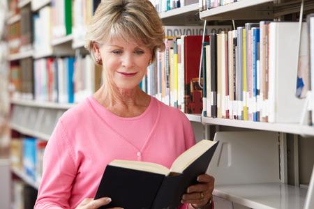 Rijpe student in de bibliotheek Stockfoto