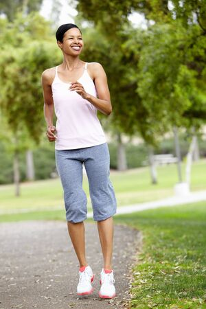 fits in: Woman jogging in park Stock Photo