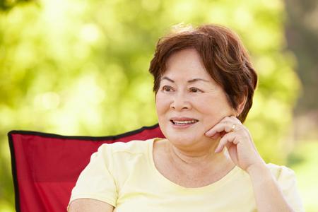 senior women: Senior Asian woman sitting outdoors