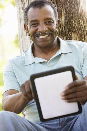 hombres maduros: Hombre mayor del afroamericano en parque usando el ordenador de la tablilla