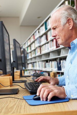 coursework: Senior man working on computer in library Stock Photo