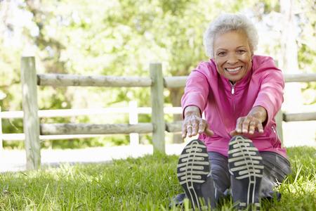 stretching: Mujer mayor del afroamericano que ejercita en parque Foto de archivo