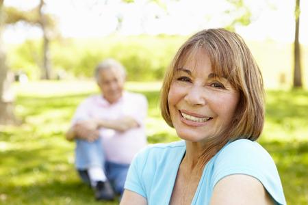 dama antigua: Pares hisp�nicos mayores que se relajan en el parque Foto de archivo