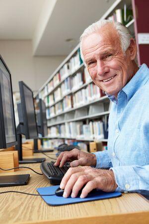 hombres maduros: Hombre mayor que trabaja en la computadora en la biblioteca