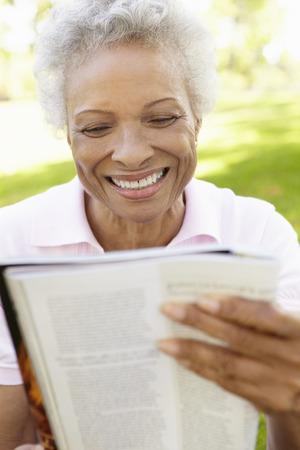 senior african: Senior African American Woman Reading Magazine In Park