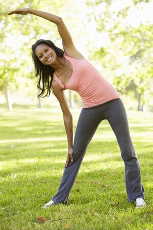 touching toes: Young African American Woman Exercising In Park Stock Photo