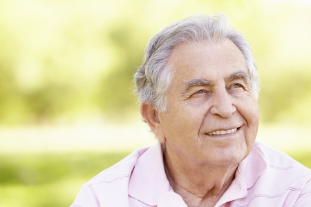 Senior Hispanic Man Relaxing In Park Stock Photo